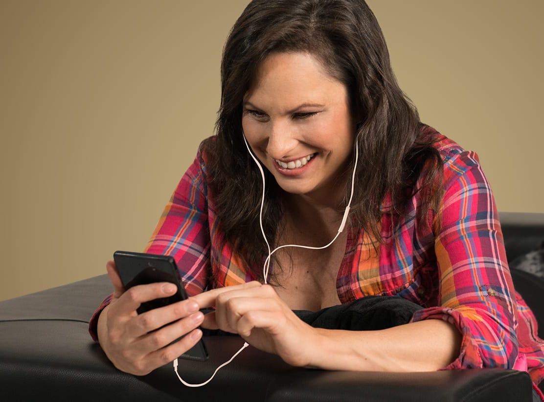 Dani Linzer liegt auf der Couch und hört Musik über Kopfhörer
